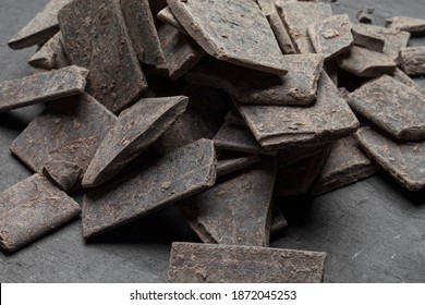 Raw 100% pure organic cocoa chocolate bar isolated on black stone background with shadow. Theobroma cocoa mass or paste