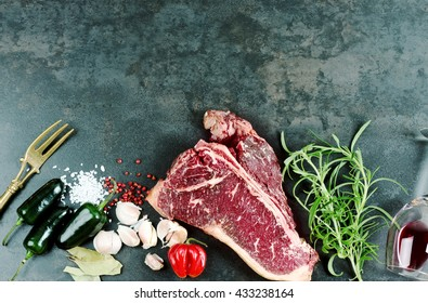 Raw aged meat T-bone steak and seasoning on dark background