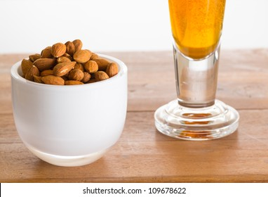 Raw almond nuts in white glass bowl on old wooden table with glass of cold beer