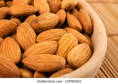 Raw almonds in wooden bowl close up