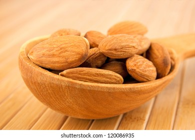 Raw almonds in wooden spoon close-up