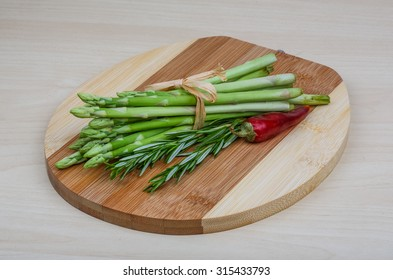 Raw asparagus heap with rosemary leaves on the wood background