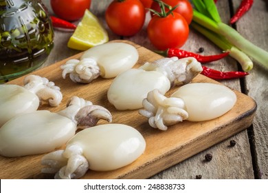 Raw babies cuttlefish  on a cutting board with tomatoes, onions, chili peppers and lemon