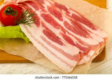 Raw bacon served dill over the wooden background