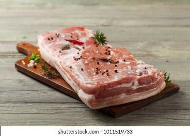 Raw bacon in whole on wooden background. Front view.