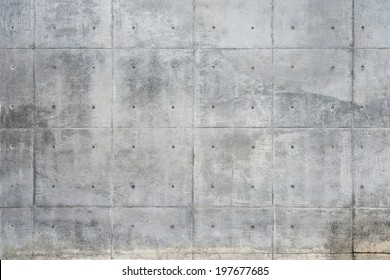 Raw or bare concrete wall, with seams and dimples.