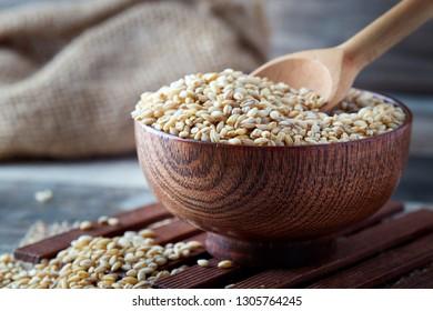 Raw barley grain (Hordeum vulgare) in wooden bowl