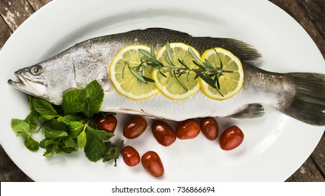 raw barramundi or asian seabass with tomatoes, sliced lemon and other gourmet on white plate. Cooking concept