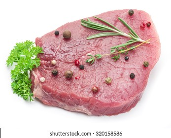 Raw beaf steaks with spices on a white background.