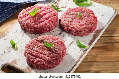 Raw beef burger patties on a wooden cutting board. Selective focus