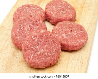 Raw beef burgers close up on a chopping board