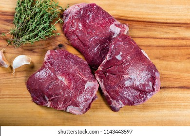 Raw beef cheeks on chopping board with herbs