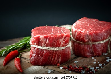 Raw beef filet Mignon steak on a wooden Board with pepper and salt, black Angus marbled meat