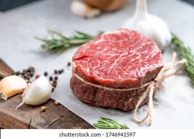 Raw beef filet Mignon steak on a wooden Board on paper with ingredients for grilling, close up