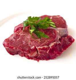 Raw beef fillet steak with sprig of parsley on white background, isolated