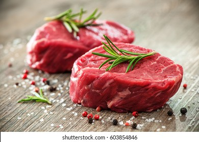 Raw beef fillet steaks with herbs and spices on wooden background