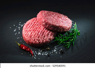 Raw beef hamburger patties with herbs and spices on dark slate plate