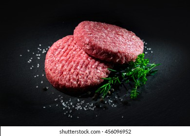 Raw beef hamburger patties with spices on dark slate plate