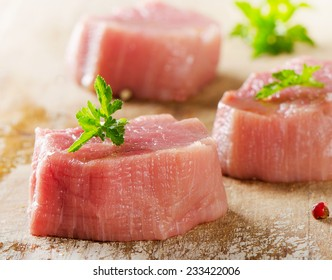 Raw beef with herbs on a wooden background. Selective focus