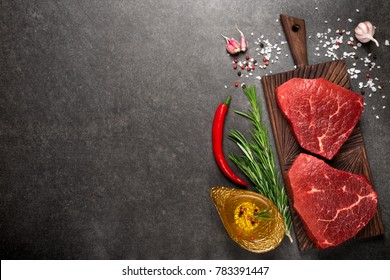 Raw beef marbled steak on cutting board with rosemary and spices. Top view and copy space