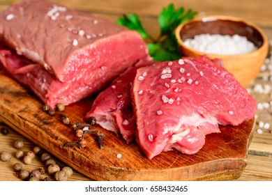 Raw beef meat on rustic wooden cutting board. Close-up.