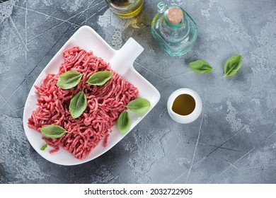 Raw beef mincemeat with seasonings on a shovel-shaped plate, flatlay on a grey concrete background, horizontal shot with copyspace