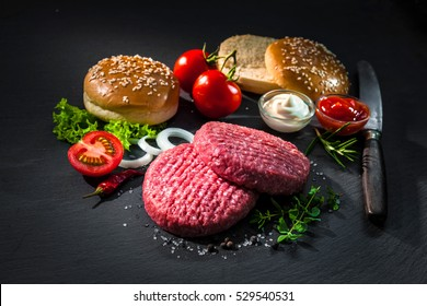 Raw beef patties, sesame buns with other ingredients for hamburgers on dark slate plate