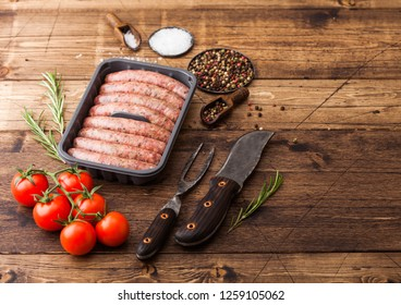 Raw beef and pork sausage in plastic tray with vintage knife and fork on wooden background.Salt and pepper with tomatoes.