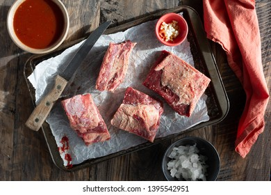 Raw beef ribs on a pan with seasoning