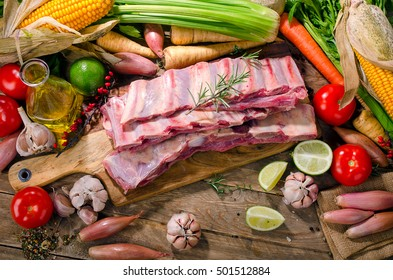 Raw beef ribs and vegetables on  wooden background. View from above