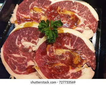 Raw beef with sauce in black tray
