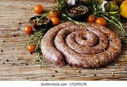 rohe Rindfleischwürste mit Rosmarin und Gewürzen auf einem Holztisch, südafrikanische Ebereien