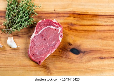 Raw beef scotch fillet steak on chopping board with herbs