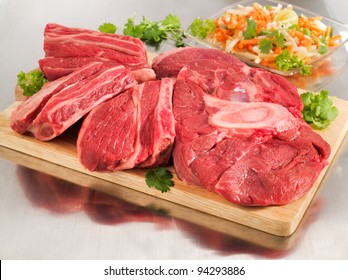 Raw beef shank steak on a cutting board and steel table.