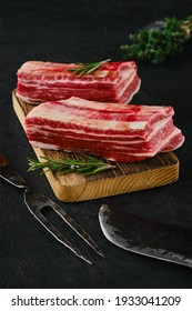 Raw beef short ribs, bone in on dark background