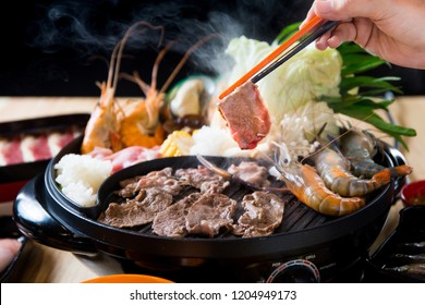 Raw beef slice for barbecue, meat are being cooked on stove or Japanese style yakiniku.