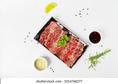 """Raw beef sliced, japanese beef sliced """"Wagyu"""" in black plate top view on white background"""