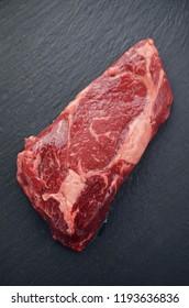 Raw beef steak on a dark table.