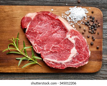 raw beef steak on wooden cutting board