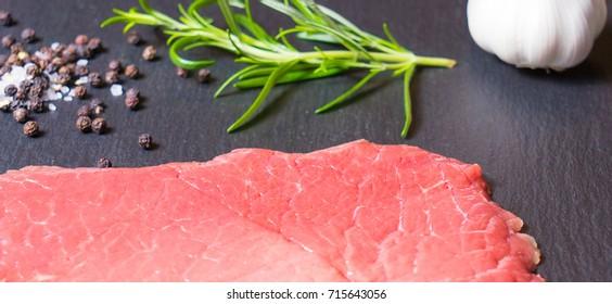 Raw Beef Steak, salt, pepper, rosemary with black background