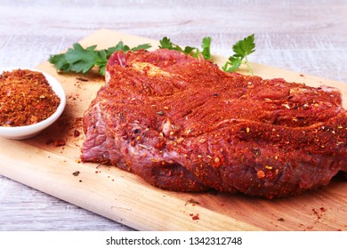 Raw beef steak with spices Leaves of coriander on wooden cutting board. Ready for cooking.