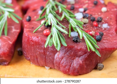raw beef steak with spices and rosemary closeup