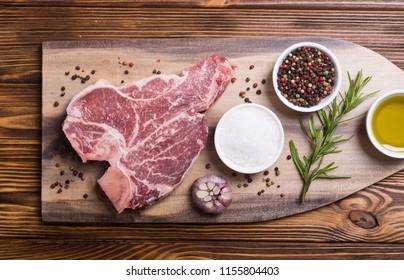 Raw beef steak T bone with ingredient . Porterhouse on cutting board .