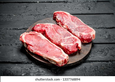 Raw beef steaks on cutting Board. On a black rustic background.