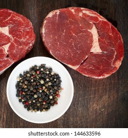 Raw beef steaks with peppercorns, on wooden board.