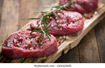 Raw beef steaks with rosemary, salt and pepper