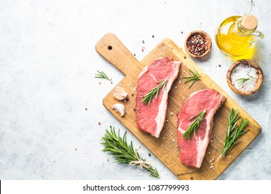 Raw beef striploin steak on cutting board.