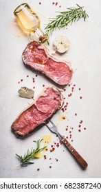 Raw beef Striploin steaks with oil , spices and meat fork on white stone background, top view, flat lay, vertical