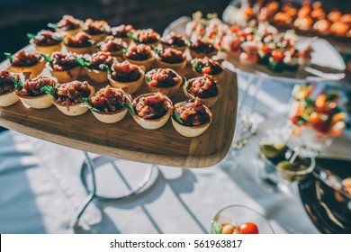Raw beef tartar mini canapes on a catering table at luxury event