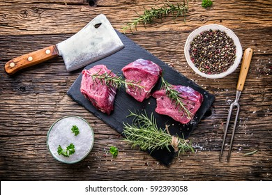 Raw beef tenderloin steak on a cutting board with rosemary pepper salt fork and cutter.